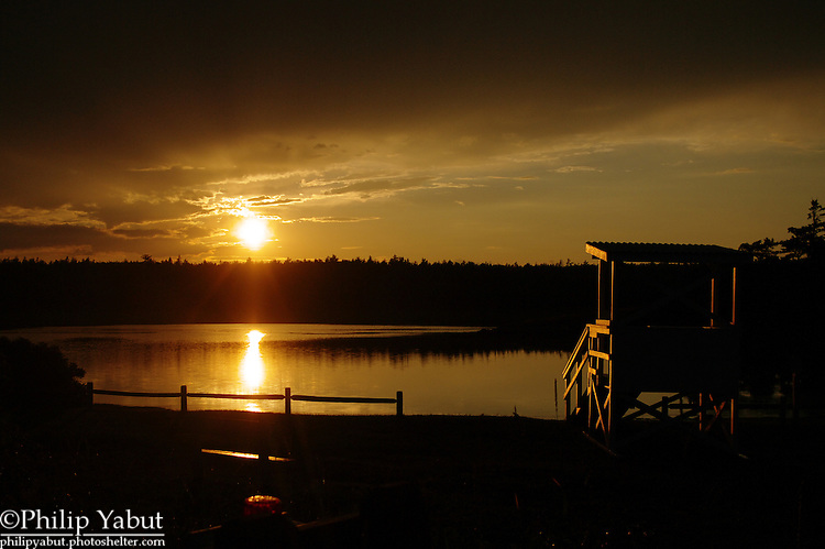 The sun sets behind a tidal pool at Reid State Park, Georgetown, Maine.