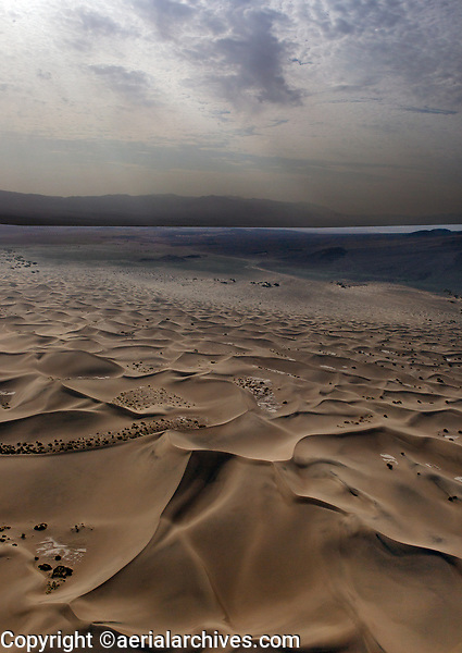 aerial photograph of the Mesquite Flat Dunes, Death Valley National Park, northern Mojave Desert, California; a summer storm passes in the north