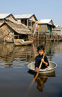 A children paddling along traveling in her washbasin or washing tub on the Tonle Sap lake, This is a way life and transportation amongst the local population especially during the Monsoon season. Going from house to house. Cambodia