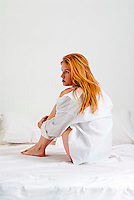 Young red haired woman sitting in bed with bare legs pulled up to her