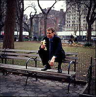 Man in suit sitting on park bench holding a banana<br />
