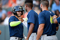 Second baseman Michael Paez (3) of the Columbia Fireflies is greeted by Jose Medina (8) and Tim Tebow (15) after hitting a home run in a game against the Greenville Drive on Thursday, June 15, 2017, at Fluor Field at the West End in Greenville, South Carolina. Columbia won, 7-2. (Tom Priddy/Four Seam Images)
