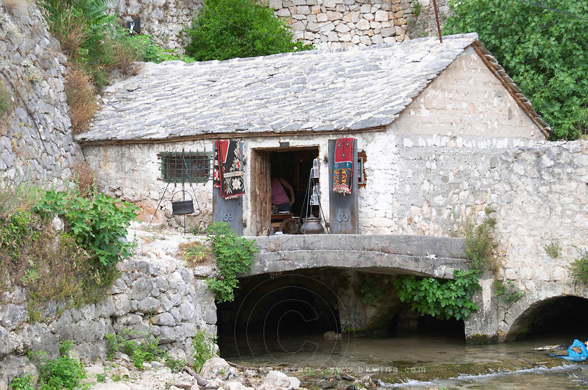The old Ottoman style water mill building with roof tiled with stone slates, now converted to a souvenir shop. The source of the Buna river and the house of the Whirling Dervishes, an old Muslim monastery, Blagaj. Federation Bosne i Hercegovine. Bosnia Herzegovina, Europe.