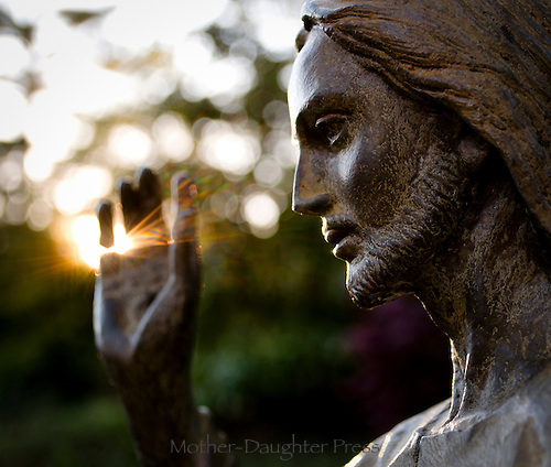 Sunrise in spring sparks light into the hand of a state of Jesus Christ, Washington DC USA