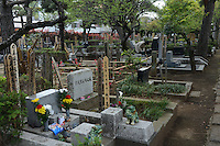 Family visits their pet grave.<br /> Individual graves for lost loved pets. Gravestones are designed with thoughts.<br /> <br /> Jikeiin is the biggest pet graveyard in western suburb of Tokyo.  This has founded in 1921 and 13000m2 land space.  They have 16 cremation machine which can cremate from small animal like turtle or birds to big animals like tigers and bears.  They provide buddism style funeral ceremony and graves to pet owners who have lost their loved pets.  Jikeiin is the non-sectarian temple.