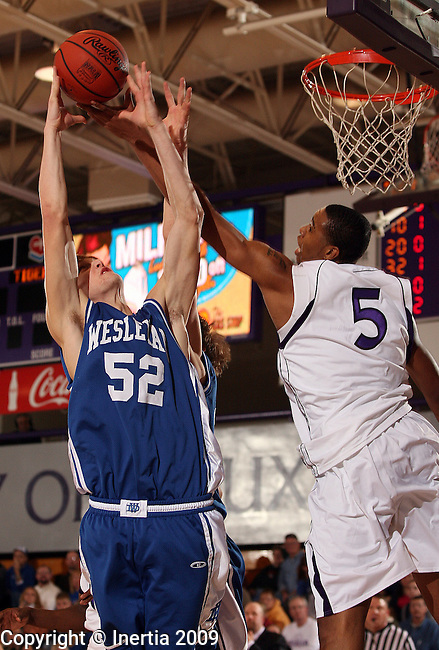 SIOUX FALLS, SD - DECEMBER 9:  Matt Dykstra #52 of Dakota Wesleyan battles for a rebound with De'Shawn Howard #5 of the University of Sioux Falls in the first half of their game Wednesday night at the Stewart Center in Sioux Falls. (Photo by Dave Eggen/Inertia)