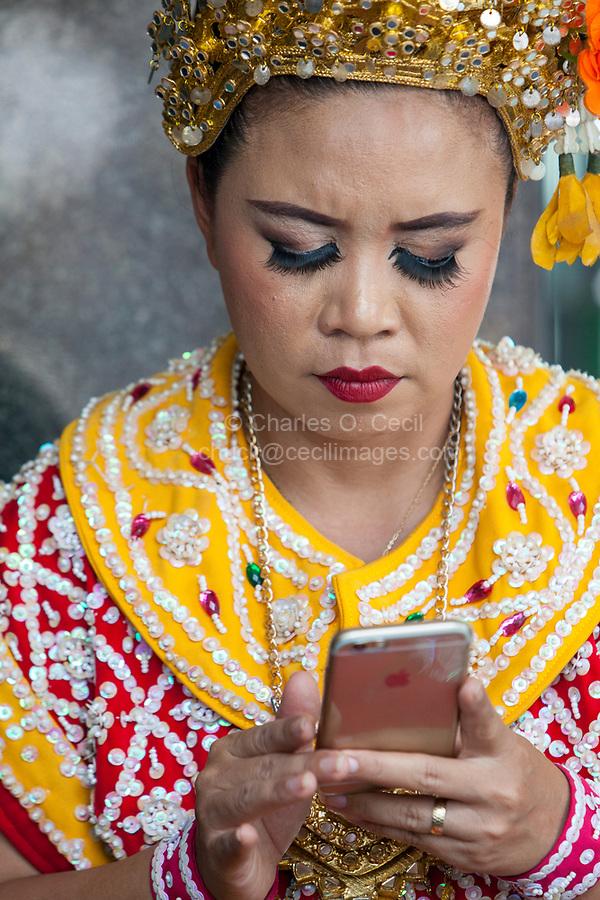 Bangkok, Thailand.  Thai dancer at the Erawan Shrine Checking her Cell Phone.