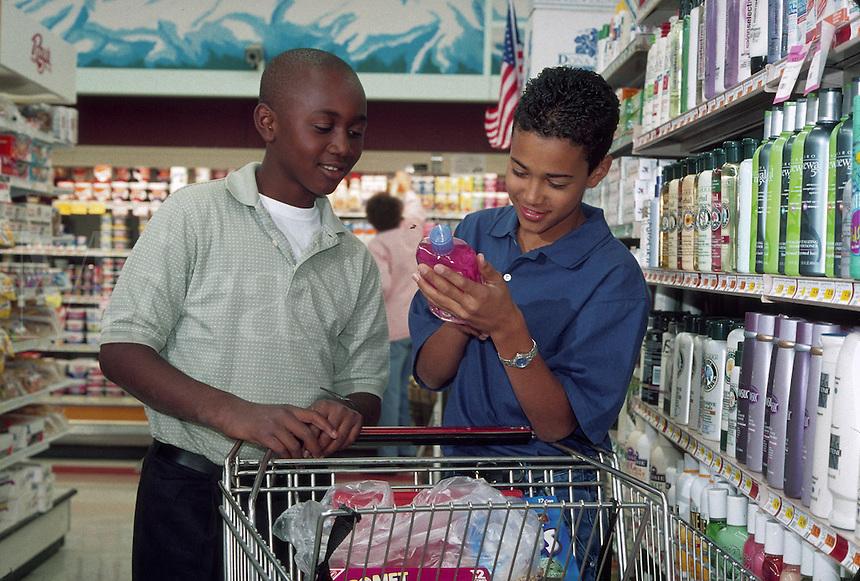 Mixed ethnic teenage boys shopping for shampoo in supermarket