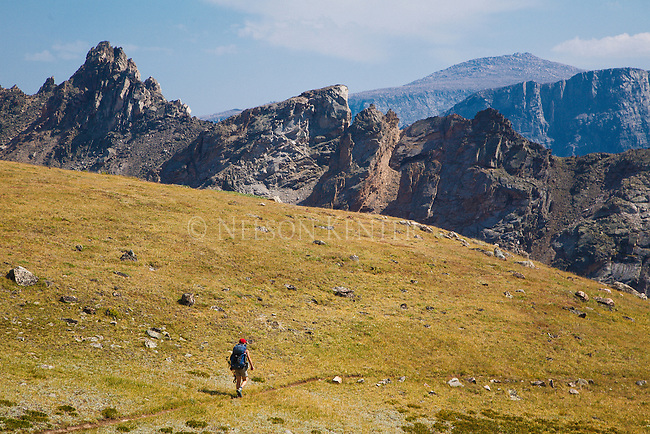a hiker at sundance pass in the absaroka beartooth wilderness in montana. mountain peaks above 12000 feet all around.