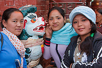 Bodhnath, Nepal.  Young Nepali Women beside Mythical Snow Leopard at Entrance to Buddhist Shrine.