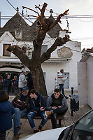 Italy. Apulia Region. Alberobello. Alberobello is a small town which is famous for its unique trullo buildings. A father and his two sons seat on a bench. On their smartphone, they check social media and social networking services. A trullo (plural, trulli) is a traditional Apulian dry stone hut with a conical roof. The structural walls of a trullo are laid directly on the bedrock. Their width varies from 0.80 to 2.70 metres. Their height (from ground level to where the vault starts) ranges from 1.60 to 2 metres. On cone's top, there is normally a hand-worked sandstone pinnacle (pinnacolo), that may be one of many designs - disk, ball, cone, bowl, polyhedron, or a combination thereof, that is supposed to be the signature of the stonemason who built the trullo. Their style of construction is specific to the Itria Valley in the Murge area. Trulli generally were constructed as temporary field shelters and storehouses or, as permanent dwellings by small proprietors or agricultural labourers. In Alberobello's town, whole districts contain dense concentrations of trulli. Trullo has replaced the local term casedda which was used by locals in the Murgia area to call this type of house, which used to be the local agricultural dry stone hut. Alberobello's trulli have been designated as a UNESCO World Heritage site since 1996. Apulia (Puglia) is a region in Southern Italy. 7.12.18  © 2018 Didier Ruef