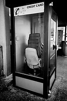 Switzerland. Canton Ticino. Lugano. A derelict Swisscom phone booth with old offices chairs piled on each other. A phone sign with various coins. The word Credit Card is written on the glass window. Lugano Airport (IATA: LUG, ICAO: LSZA) is a regional airport located 4 km west of the city of Lugano. It lies closer to the town of Agno than to Lugano itself, and is sometimes known as Lugano-Agno.17.04.2020 © 2020 Didier Ruef
