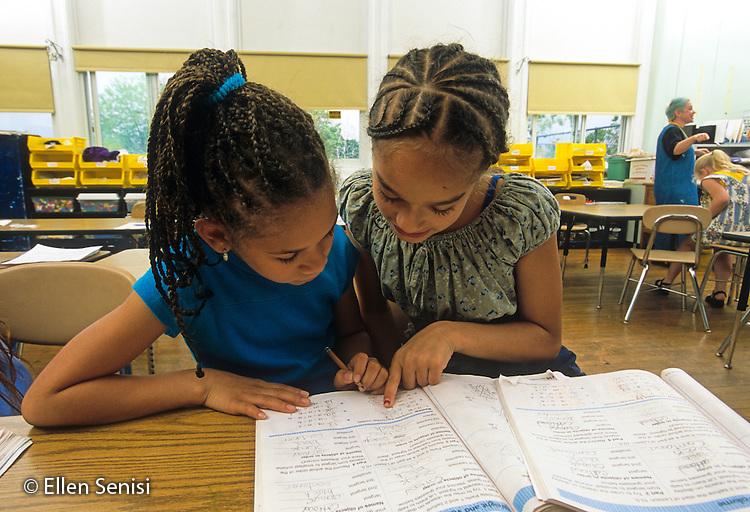 MR / Schenectady, New York. Yates Arts in Education Magnet School (urban public school).Grade 3. Students (girl right: 8, Puerto-Rican-American)(girl left: 8) work together on assignment in math workbook. ID: L-C. MR: Rod5, Ser1 ©Ellen B. Senisi