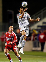 FC Dallas defender Alex Yi (21) heads the ball away as Chicago Fire forward Chad Barrett (9) looks on.  FC Dallas defeated the Chicago Fire 2-1 at Toyota Park in Bridgeview, IL on May 17, 2007.