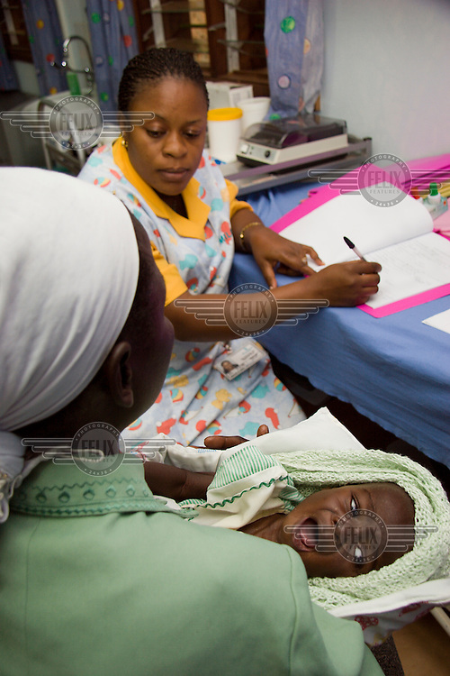 Nurse Rose treats a baby with HIV/AIDS at Mildmay hospital. Mildmay is an international HIV/AIDS charity, specialising in care, training and service development within this field.