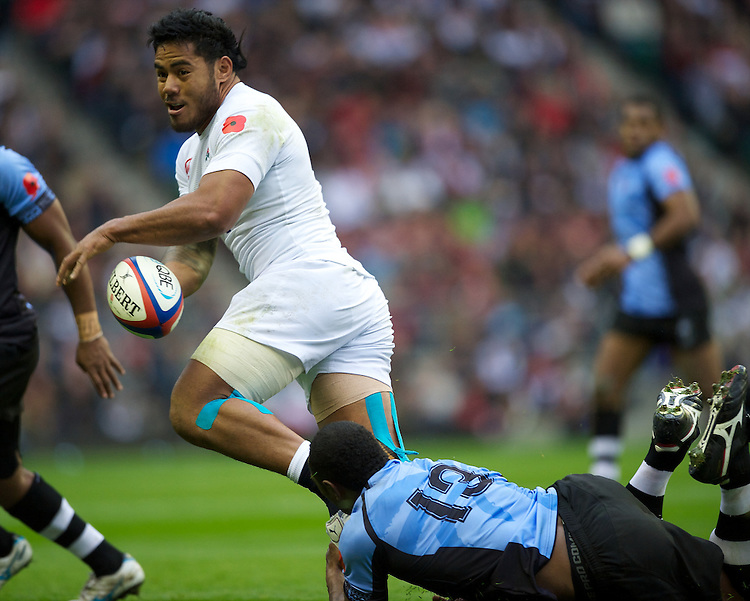 Manu Tuilagi of England offloads as he is tackled by Vereniki Goneva of the Flying Fijians during the QBE International between England and Fiji at Twickenham on Saturday 10th November 2012 (Photo by Rob Munro)