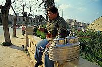 Street vendor selling tea on the sidewalk in Aleppo, Syria.