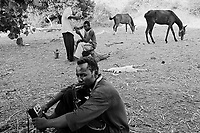 Western Sudan, June 15, 2004.A group from 'SLA' rebels near the border with Tchad. A rebel listens to 'The Voice of Sudan', an opposition radio network based in Asmara, Erythrea while another one gets a haircut.