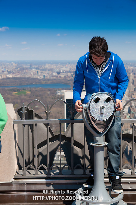 Guy playing with binoculars on Top Of the Rock observation deck with Central Park on background