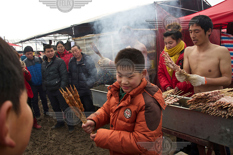 A food stall selling kebabs at the site of the Ma Jie folk festival. <br /> <br /> For centuries farmers in Henan have gathered during Chinese New Year in the region's wheat fields to listen to bards singing and recounting old tales. <br /> <br /> Now storytellers come from all over China to attend the annual festival where large crowds gather to watch the best performers.
