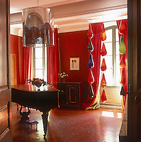 A dramatic red room with floor to ceiling curtains and a hexagonal tiled floor. Large coloured glass lights hang at one window and a baby grand piano stands in the centre of the room.