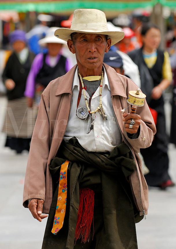 Tibetan pilgrim with prayer wheel, rosary beads and amulet, walking the Barkhor prayer circuit around the Jokhang Temple, during Saga Dawa festival, Lhasa, Tibet.