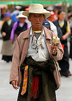 Tibetan pilgrim with prayer wheel, rosary beads and amulet, walking the Barkhor prayer circuit around the Jokhang Temple, during Saga Dawa festival, Lhasa, Tibet.