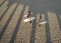 The shadow from Hunnington Beach Pier hangs over surfers walking along the beach.