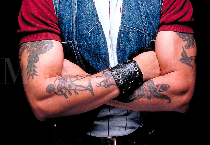 Young man with tatooed arms.