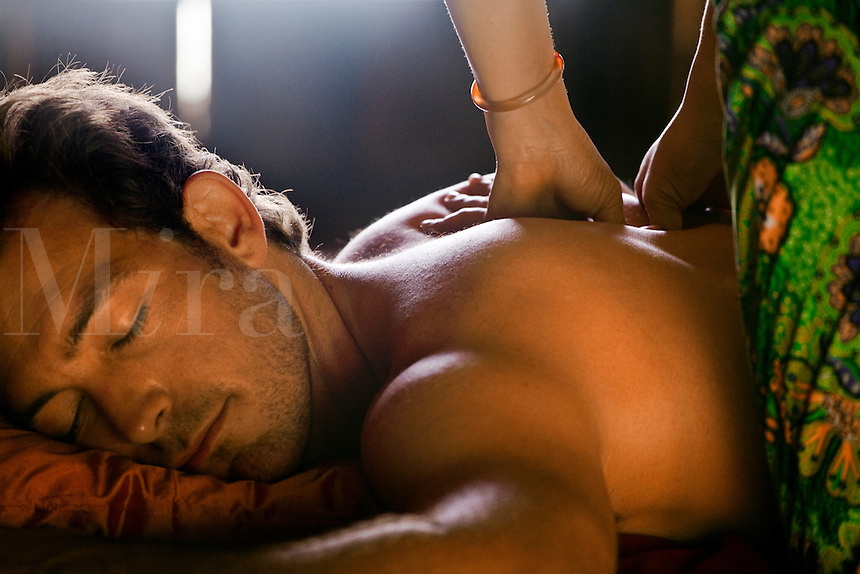 A TOURIST enjoys a THAI MASSAGE at a beach resort - BANGKOK, THAILAND (MR)