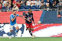 FOXBOROUGH, MA - SEPTEMBER 11: Teal Bunbury #10 of New England Revolution dribbles down the wing as Maxime Chanot #4 of New York City FC pressures during a game between New York City FC and New England Revolution at Gillette Stadium on September 11, 2021 in Foxborough, Massachusetts.