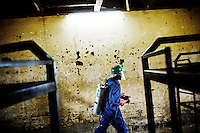 A man from the NGO Malaria Consortium spraying insecticide on the walls of a boarding school in the Gulu region of Uganda in order to protect children from malaria. Spraying of insecticides inside homes (known as indoor residual spraying) is one of the ways to prevent malaria. The insecticide, sprayed on the walls, acts as a repellent and kills any mosquitoes that land there..