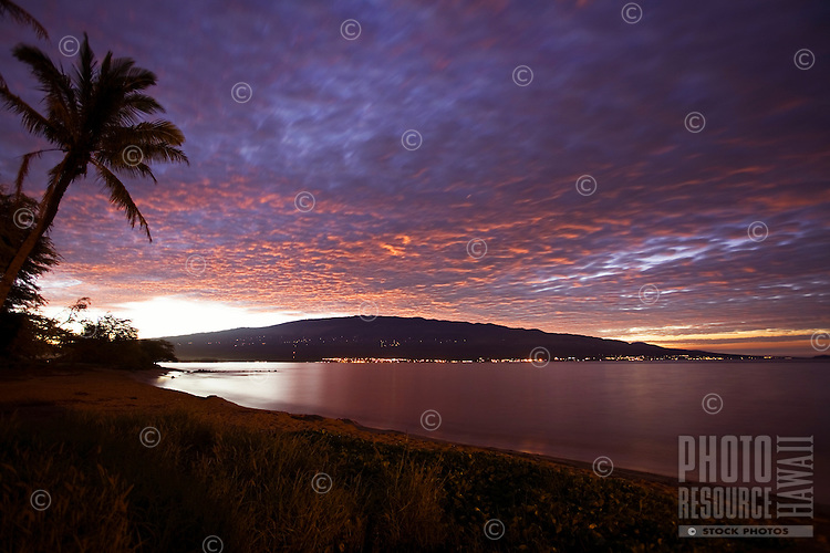 The view from Maalaea, Maui.  Kihei and Wailea lights line the shore in the distance while a colorful sunrise blankets Mount Haleakala.