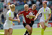 Mandy Marchak of Canada accelerates through Michaela Staniford (left) and JoanneWatmoreof England during the iRB Challenge Cup at Twickenham on Sunday 13th May 2012 (Photo by Rob Munro)