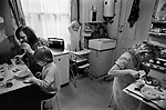 Working class family at home Fulham London 1972. This is their kitchen. They did not have their own bathroom which was shared with other families in the house.The kitchen table is not big enough for everyone to sit around. Mother uses the small pull down 'table' when they all eat together.
