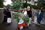 Chelsea Flowers Show last day taking home flowers sold cheaply at the end of the show London Uk 1997. Pushing flowers bought towards Chelsea Bridge and the car park on the other side.
