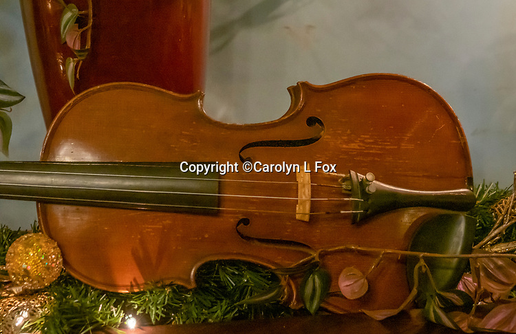 An antique violin lays on a table.