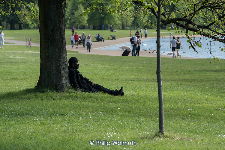 Man resting under a tree, Kensington Gardens, London.
