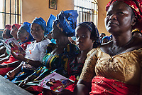 Nigeria. Enugu State. Awhun. Saint Luke's Catholic Parish. Igbo religious wedding ceremony. Blessing Amusiogo is the bride, and Michael Ogbo the groom. Friends and family relatives of the couple are seated on the first rows in the church. All women were a head tie which is a women's cloth head scarf. The head tie is used as an ornamental head covering or fashion accessory, or for functionality in different settings. Its use or meaning can vary depending on the country and/or religion of those who wear it. The head tie is called gele in Nigeria. 29.06.19 © 2019 Didier Ruef