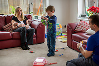 A woman sitting on her living room sofa and breastfeeding her 2 month old baby daughter while her older boy plays with a transformer toy.<br /> <br /> Hampshire, England, UK<br /> 10/02/2013