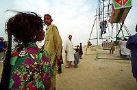 A girl is standing in front of a merry-go-round in the desert of Cholistan at the Sufi-Shrine near Chenepir. The people came from far away to have a ride.<br /> 16.2.2001, Chenepir/Punjab<br /> Copyright: Christian-Ditsch.de<br /> [Inhaltsveraendernde Manipulation des Fotos nur nach ausdruecklicher Genehmigung des Fotografen. Vereinbarungen ueber Abtretung von Persoenlichkeitsrechten/Model Release der abgebildeten Person/Personen liegen nicht vor. NO MODEL RELEASE! Nur fuer Redaktionelle Zwecke. Don't publish without copyright Christian-Ditsch.de, Veroeffentlichung nur mit Fotografennennung, sowie gegen Honorar, MwSt. und Beleg. Konto: I N G - D i B a, IBAN DE58500105175400192269, BIC INGDDEFFXXX, Kontakt: post@christian-ditsch.de<br /> Bei der Bearbeitung der Dateiinformationen darf die Urheberkennzeichnung in den EXIF- und  IPTC-Daten nicht entfernt werden, diese sind in digitalen Medien nach §95c UrhG rechtlich geschuetzt. Der Urhebervermerk wird gemaess §13 UrhG verlangt.]