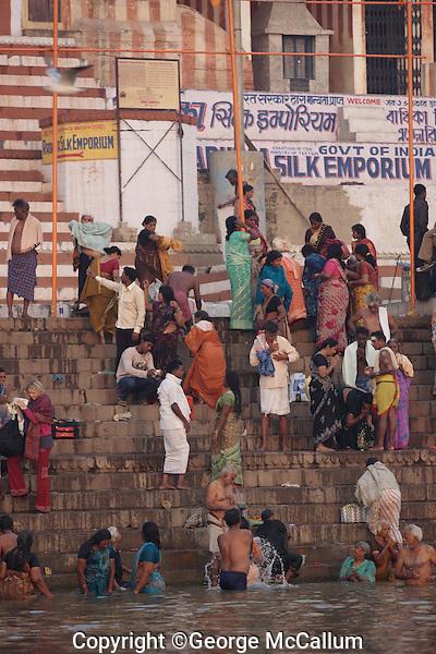 Men and women performing morning puja or prayers in Ganges river,  Kebra Ghat, Varanasi, India