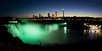 Amazing Niagara Falls panorama with water lit up in green under a clear blue and orange sky, USA and Canada