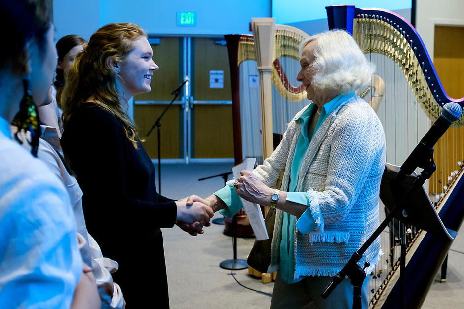 Erin Baker, left, shakes hands with USA International Harp Competition Founder and Artistic Director Susann McDonald before the Composition Forum at the 11th USA International Harp Competition at Indiana University in Bloomington, Indiana on Monday, July 8, 2019. (Photo by James Brosher)