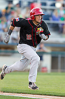 Michael De La Cruz #12 of the Vancouver Canadians hustles down the first base line during a game against the Everett AquaSox at Everett Memorial Stadium in Everett, Washington on July 9, 2014.  Everett defeated Vancouver 9-4.  (Ronnie Allen/Four Seam Images)