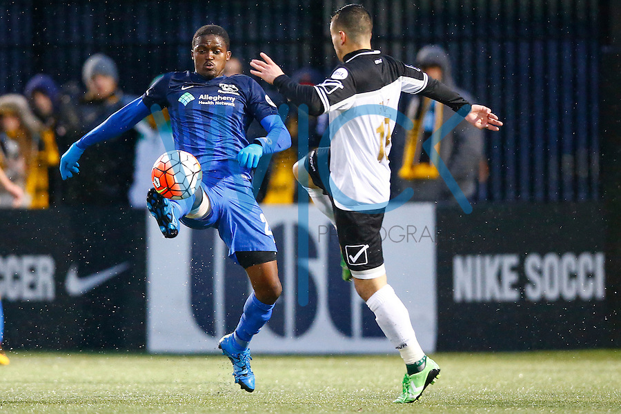 Lebo Moloto #22 of the Pittsburgh Riverhounds passes the ball off in front of Michael Garzi #13 of the Rochester Rhinos in the first half during the match at Highmark Stadium in Pittsburgh, Pennsylvania on April 2, 2016. (Photo by Jared Wickerham / DKPS)
