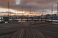 The view looking west on the wooden public observation platform at the San Leandro Marina at sunset on a cloudy autumn evening.  The platform's design is, itself, a bit of geometric art.