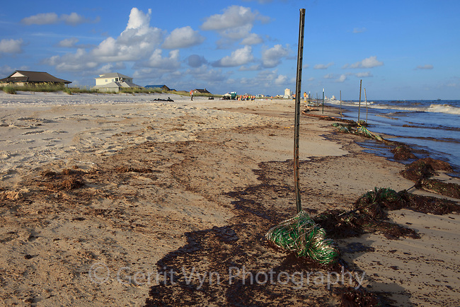 """Oiled beach and an improvised """"pom-pom"""" boom used to capture oil as it comes ashore. Baldwin County, Alabama. June 2010."""