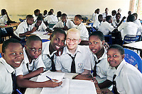 """15 year old Joyce studying in class with her school friends. Her mother is a nurse, so knew how to take care of her and her brother, """"I knew how to take care of the skin. Especially when they are young, albinos should be very well cared for. I always kept them inside and lotioned their skin on a daily basis."""" Even with the protection of a knowledgeable and loving mother, Joyce was recently terrified while waiting for the school bus. She overheard two men saying how they should kidnap her in order to sell her hair and skin. Discrimination against albinos is a serious problem throughout sub-Saharan Africa, but recently in Tanzania albinos have been killed and mutilated, victims of a growing criminal trade in albino body parts fuelled by superstition and greed. Limbs, skin, hair, genitals and blood are believed by witch doctors to bring good luck, and are sold to clients for large sums of money, carrying with them the promise of instant wealth."""