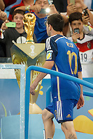 Lionel Messi of Argentina walks past the World Cup trophy